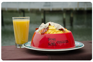 A classic Salty Dog breakfast including eggs, bacon, home fries,              cheese and hollandaise served in a souvenir dog bowl.